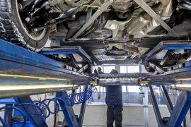 Garagiste qui réalise le contrôle technique d'une voiture en vérifiant ses pneus